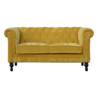 This beautiful 2 Seater Chesterfield Sofa has been upholstered in a luxurious mustard cotton velvet and features 4 turned feet constructed from 100% solid mango wood in a chestnut finish. This sofa is detailed with deep button tufts, piping and sheltering arms. This statement piece for the home can be added as a pop of colour to any room in the home or can be suited well with many different styles and colours of interiors being modern or classic.